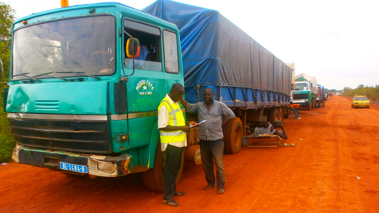 Samba Touray chatting with truck driver Modou Faye near his truck.